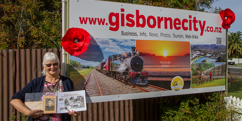 Gisborne city. Beth with Poppies on Sign 'We shall remember them""